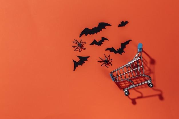 Koszyk z nietoperzami i pająkami na pomarańczowym jasnym tle. motyw halloween.