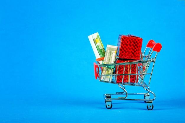 Koszyk z pieniędzmi i pudełka z prezentami. handel internetowy.