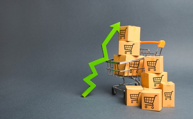 Koszyk z pudełkami kartonowymi z wzorem wózków handlowych i zieloną strzałką w górę