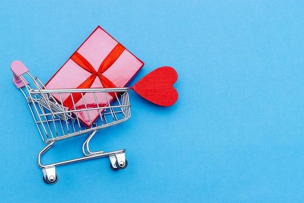Koszyk z pudełkiem i sercem. kupowanie prezentów na walentynki.
