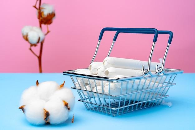 Koszyk z tamponami medycznymi na różowym i niebieskim tle