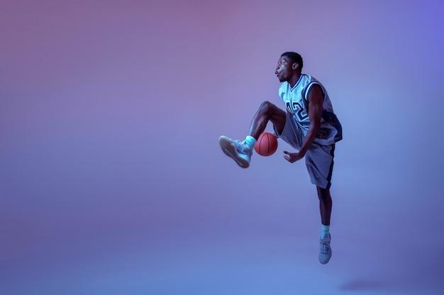 Koszykarz ćwiczy z piłką. profesjonalny męski baler w odzieży sportowej grający w grę sportową, sportowiec
