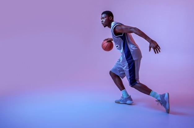 Koszykarz ćwiczy z piłką. profesjonalny męski baler w odzieży sportowej grający w sportową grę, wysoki sportowiec