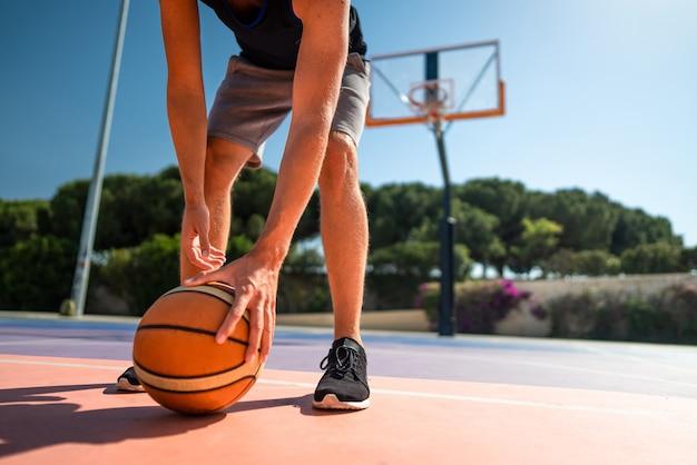 Koszykarz na placu zabaw podnosi piłkę z ziemi