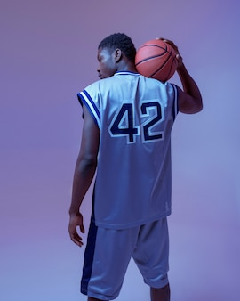 Koszykarz pozuje z piłką, widok z tyłu. profesjonalny męski baler w odzieży sportowej grający w sportową grę, wysoki sportowiec