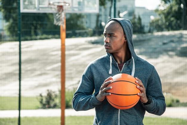 Koszykówka. poważny młody człowiek trzyma piłkę do koszykówki podczas gry