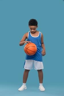 Koszykówka, rozgrzewka. afroamerykański chłopiec w sportowej odzieży stojącej, skoncentrowany uderzając piłkę ręką, ćwicząc