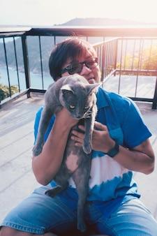 Kot trzymany przez człowieka, śmieszna twarz szary kot