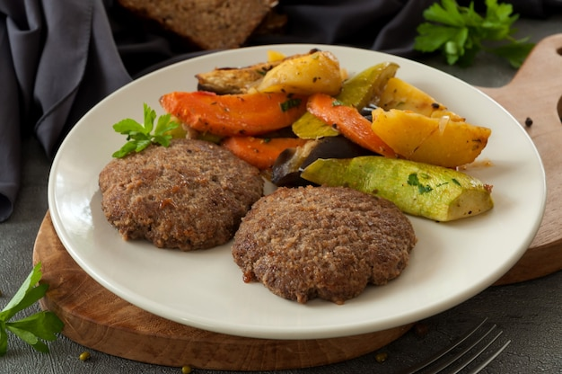 Kotleciki wołowe z pieczonymi warzywami na szarym talerzu