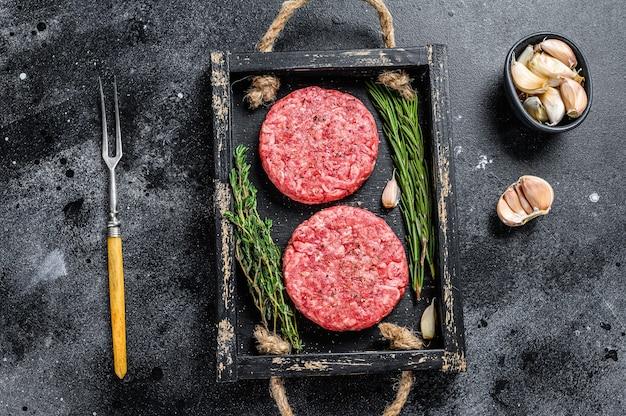 Kotleciki z surowego mięsa wołowego na burgera z mielonego mięsa i ziół na drewnianej desce. czarne tło. widok z góry.