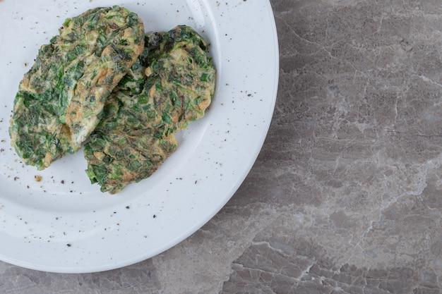 Kotlet jajeczny z zieleniną na białym talerzu.