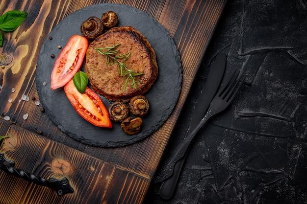 Kotlet mięsny z grzybami i rozmarynem na talerzu łupków i czarnym tle. wolne miejsce na twój tekst. wysokiej jakości zdjęcie