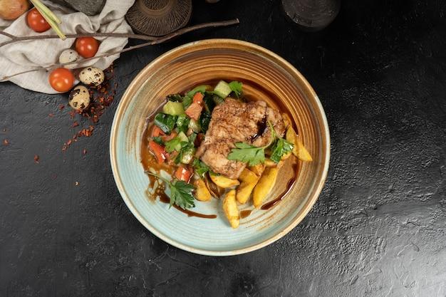 Kotlet schabowy z pieczonymi talarkami ziemniaczanymi i sałatką warzywną z pomidorów i ogórków