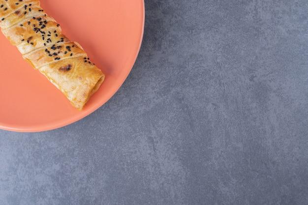 Kotlet sezamowy na talerzu, na marmurze.