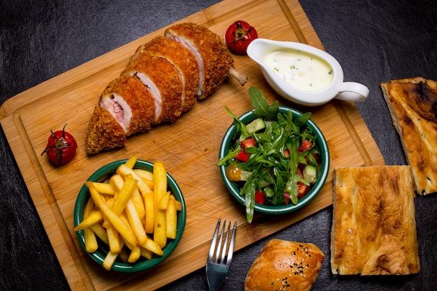Kotlet w stylu kijowskim na drewnianej desce z frytkami rukolą pomidorowy sos ogórkowy widok z góry