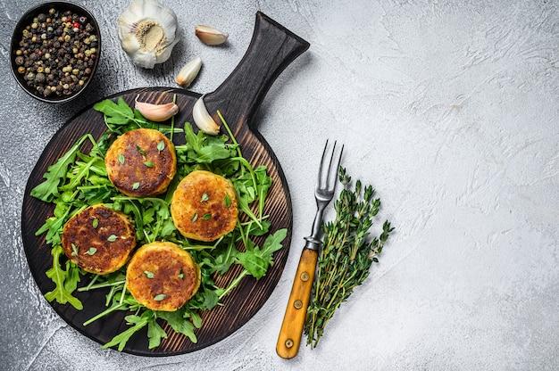 Kotlet wegetariański z soczewicą, warzywami i rukolą. biały stół. widok z góry. skopiuj miejsce.