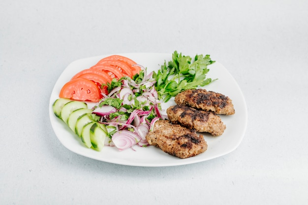 Kotlet z kurczaka z warzywami i zieloną sałatą.