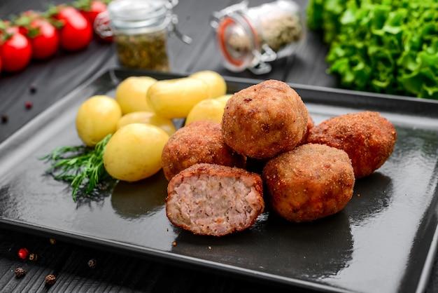 Kotlet z ziemniakami gotowanymi na czarnym talerzu, na czarnej powierzchni