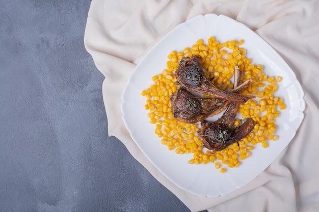 Kotlety jagnięce na białym talerzu z gotowanymi kukurydzami i satynowym obrusem na niebiesko.