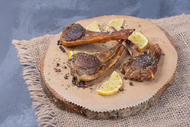 Kotlety jagnięce na drewnianej desce z plasterkami cytryny i sztućcami na obrusie.