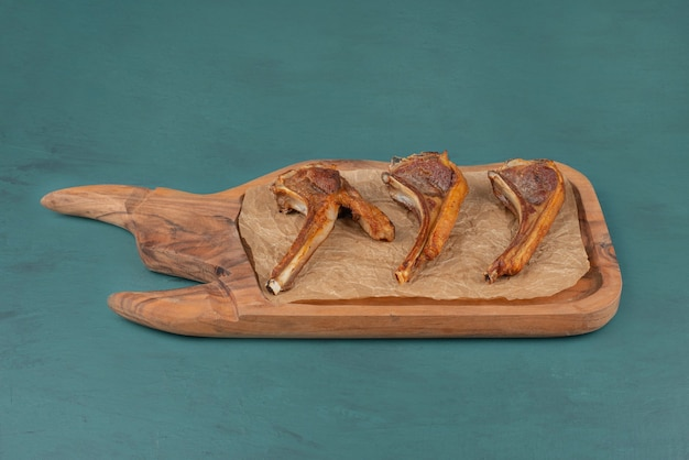 Kotlety jagnięce z grilla na drewnianej desce.