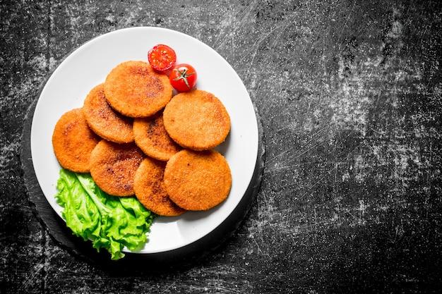 Kotlety rybne na talerzu z liśćmi sałaty i pomidorami. na czarnym tle rustykalnym