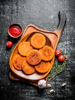 Kotlety rybne na talerzu z tymiankiem, czosnkiem i sosem pomidorowym.