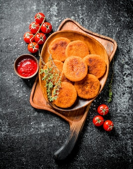 Kotlety rybne na talerzu z tymiankiem, pomidorami i sosem na czarnym drewnianym stole