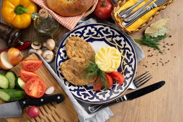 Kotlety rybne z puree ziemniaczanym, warzywami i koperkiem na talerzu z tradycyjnym uzbeckim