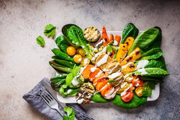 Kotlety warzywne, sos pomidorowy, awokado i grillowane warzywa na szarym talerzu. gotowanie zdrowe jedzenie wegetariańskie koncepcja.