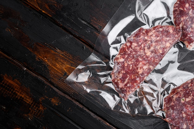 Kotlety wołowe cielęce w zestawie próżniowym plastikowym opakowaniu, na starym ciemnym tle drewnianego stołu, widok z góry płaski, z miejscem na kopię