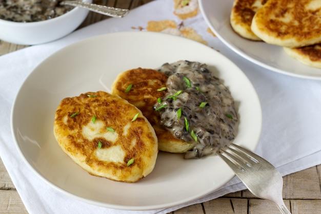 Kotlety ziemniaczane lub naleśniki z sosem grzybowym i zieloną cebulą. styl rustykalny.