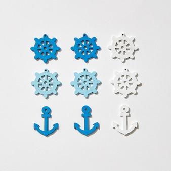 Kotwice statków i koła różnych kolorów wzór na jasnoszarym z twardymi cieniami, kopia przestrzeń. leżał na płasko