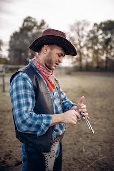 Kowboj sprawdza swój rewolwer przed strzelaniną na ranczo na zachodzie. vintage mężczyzna z pistoletem na farmie, przygoda na dzikim zachodzie