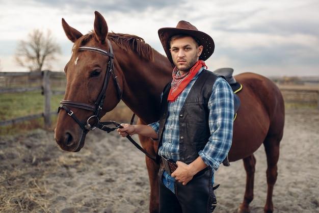 Kowboj w dżinsach i skórzanej kurtce pozuje z koniem na farmie teksasu