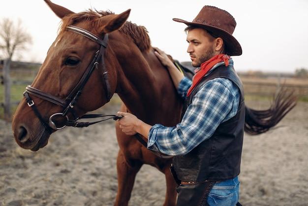 Kowboj w dżinsach i skórzanej kurtce pozuje z koniem na ranczo w teksasie