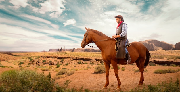Kowboj w skórzanych ubraniach jedzie na koniu w pustynnej dolinie, western. vintage mężczyzna jeździec na koniu, przygoda na dzikim zachodzie