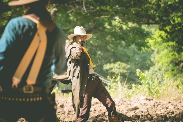 Kowboj z pistoletem przygotowuje się do strzelaniny.