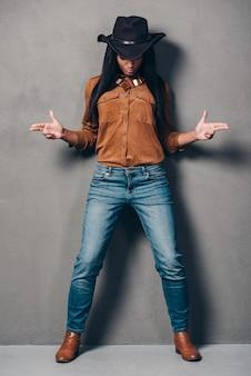 Kowbojka. pełna długość pięknej młodej afrykańskiej kobiety w kapeluszu, gestykulującej z pistoletów i patrzącej w dół