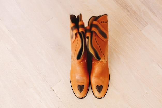 Kowbojskie buty stoją na drewnianej podłodze
