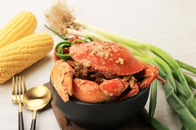 Krab błotny chili, krab w sosie singapurskim, specjalna kuchnia singapurska. podawany na czarnej misce ze złotą łyżką i widelcem