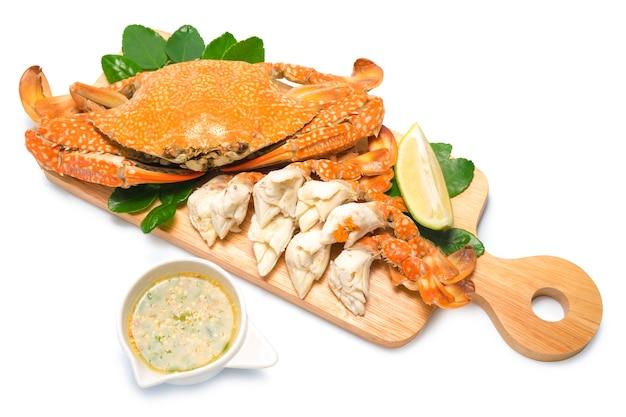 Krab gotowany na parze z pikantnym sosem z owoców morza na drewnianym talerzu. krab niebieski na parze z pikantnym dipem, po tajsku, owoce morza.