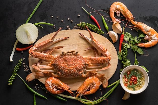 Krab i krewetki gotowane owoce morza na desce z dodatkiem sosu chili