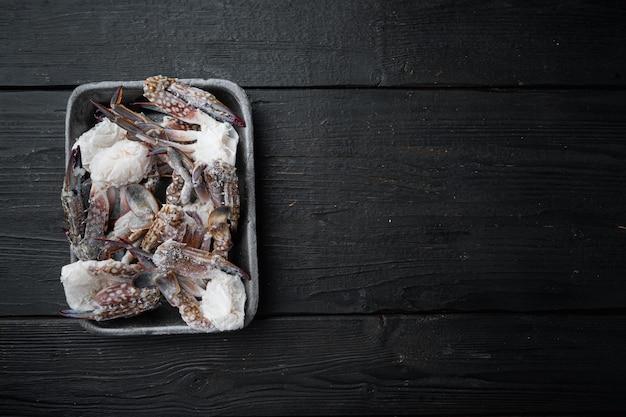Krab koński, krab niebieski, krab kwiatowy zamrożony w zestawie lodu, w plastikowej tacy, na tle czarnego drewnianego stołu, widok z góry na płasko, z copyspace i miejscem na tekst