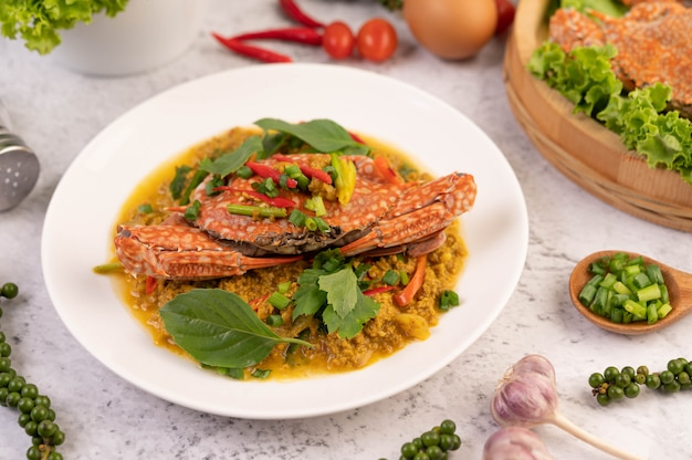 Krab smażony w proszku curry na białym talerzu na posadzce cementowej.