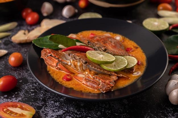 Krab tom yum z cytryną, chili, pomidorem, czosnkiem, trawą cytrynową, liśćmi limonki kaffir na talerzu