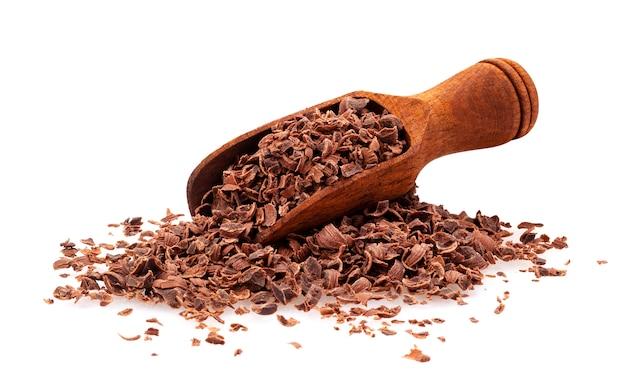 Kraciasta czekolada, stos zmielona czekolada z drewnianą miarką odizolowywającą na bielu, zbliżenie