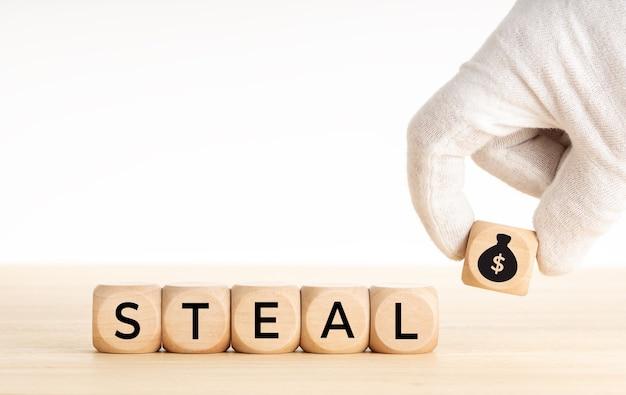 Kradnij koncepcję. ręcznie, wybierając ikonę worek pieniędzy odrobina drewniany blok i tekst na drewnianych kostkach. skopiuj miejsce.