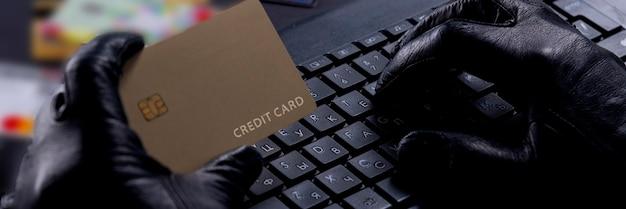 Kradzież internetu - ręce w rękawiczkach złodzieja kartą kredytową za laptopem