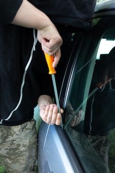 Kradzież samochodu. mężczyzna otwiera drzwi. carjacking pojazdu. rabunek i przestępczość.